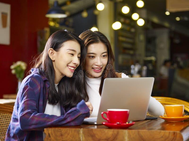 Två unga asiatiska kvinnor som använder bärbara datorn i coffee shop royaltyfria bilder