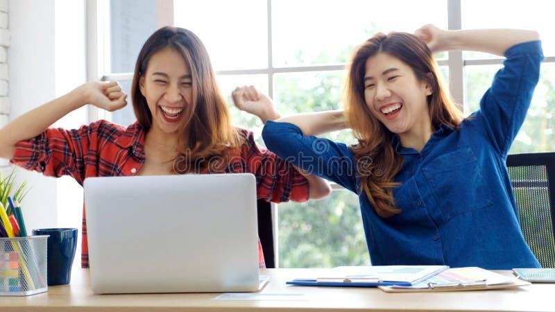 Två unga asiatiska kvinnor som använder upp bärbar datordatoren och armar med att le framsidan, medan arbeta det hemmastadda kont royaltyfri fotografi