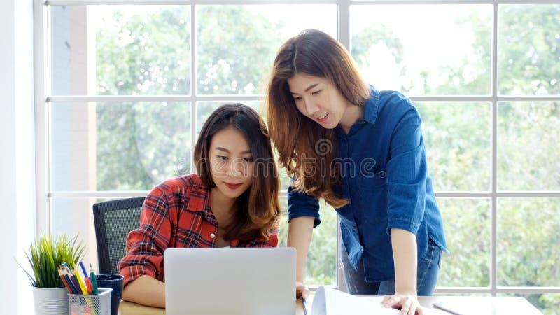 Två unga asiatiska kvinnor som arbetar med det hemmastadda kontoret för bärbar datordator med lycklig sinnesrörelse, arbeta som ä arkivfoto