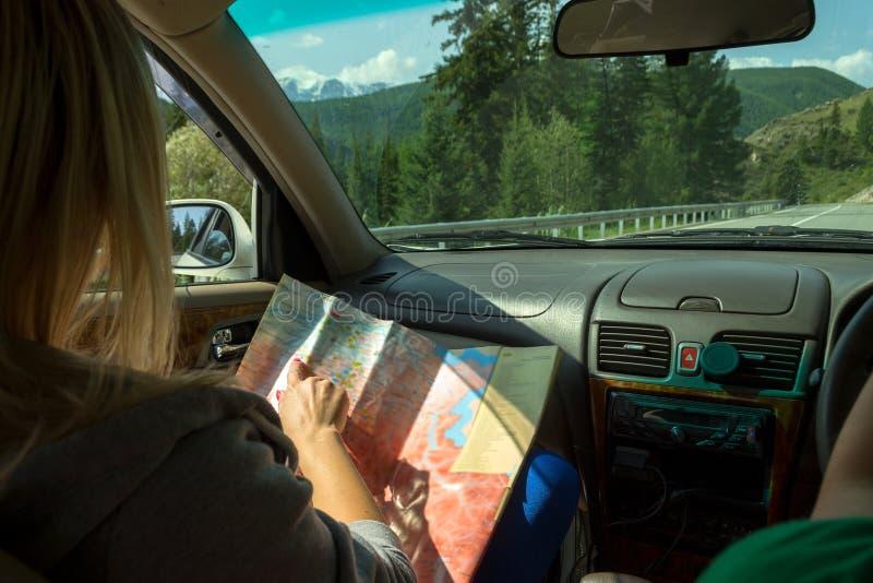 Två unga attraktiva flickor reser med bilen bland bergcoven arkivbild