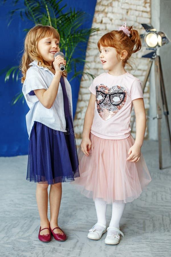 Två unga barn sjunger en sång på en mikrofon grupp Concen royaltyfri fotografi