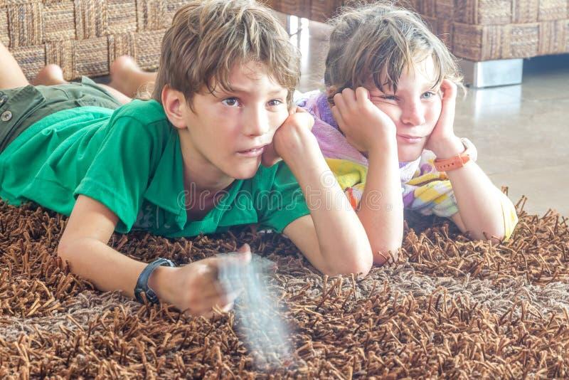 Två unga barn som håller ögonen på tv arkivfoton