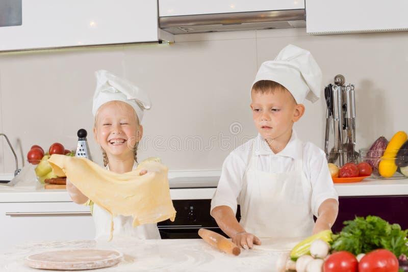 Två unga barn som har rolig danandepizza fotografering för bildbyråer