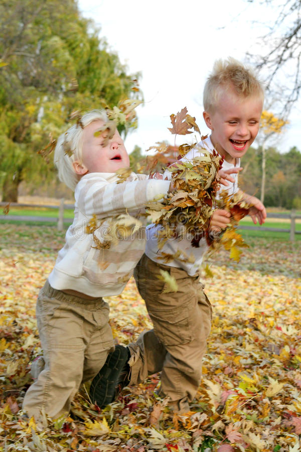 Två unga barn som kastar nedgången, lämnar utanför arkivfoton