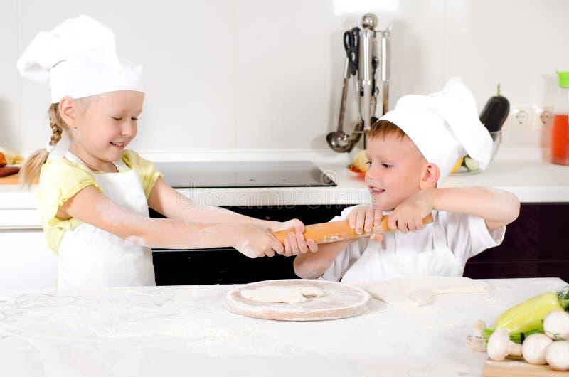 Två unga barn som slåss över en kavel arkivfoton