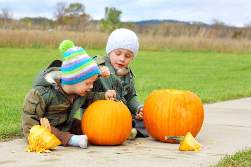 Två unga barn som snider pumpor royaltyfria foton