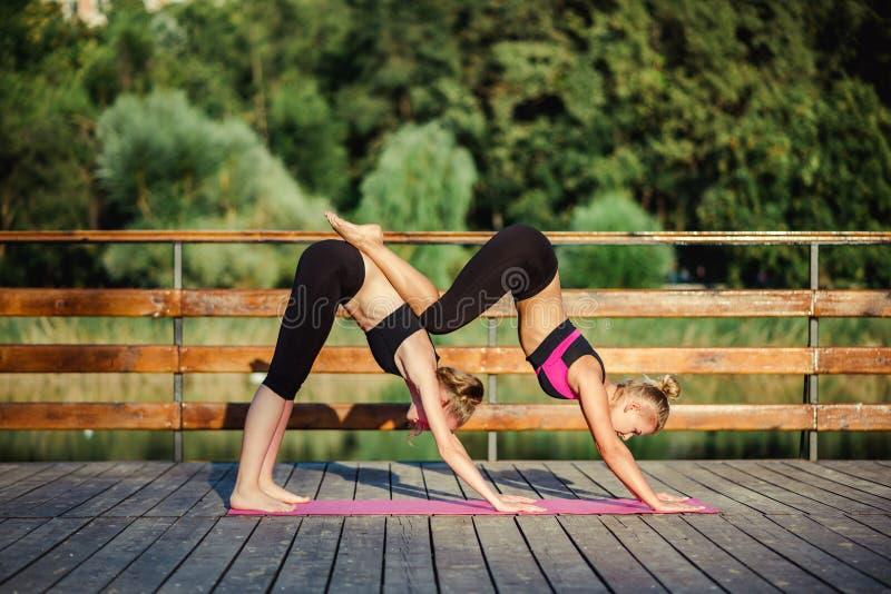Två unga Caucasian kvinnor som yogin som gör jämvikt tillbaka, sträcker acroyoga, poserar Kvinnor som gör sträcka genomkörare par royaltyfri fotografi