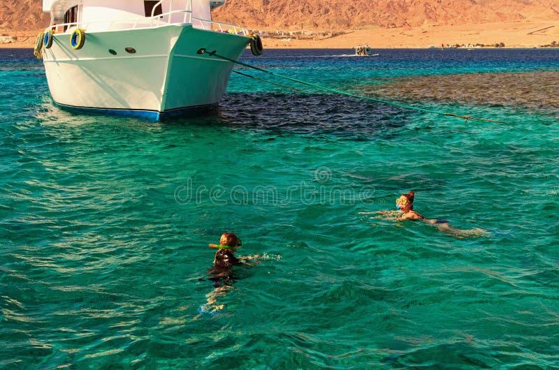 Två unga damer snorklar i rent vatten över reven nära den förtöjde yachten Lopp- och turismbegrepp Röda havet Dahab, Egypten fotografering för bildbyråer