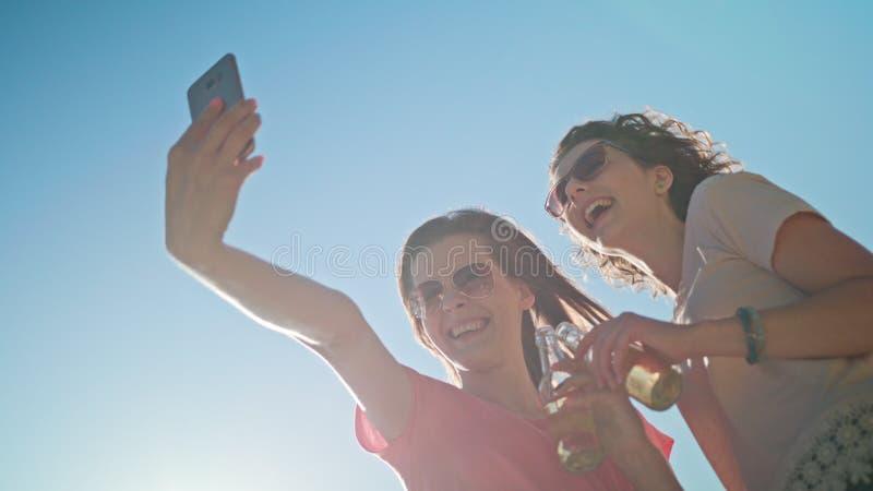Två unga damer som gör en Selfie på stranden arkivfoton