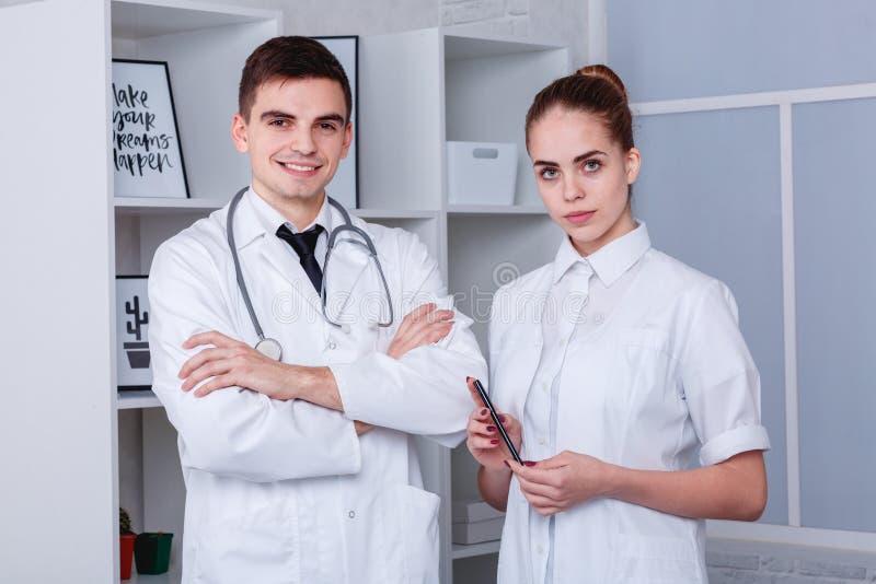 Två unga doktorer i en vit medicinsk ämbetsdräkt som poserar att stå Begreppet av medicin fotografering för bildbyråer