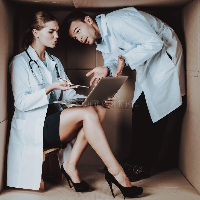 Två unga doktorer i vita lag i kartong arkivfoton