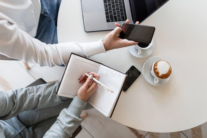 Två unga entreprenörer en man och en kvinna sitter på en tabell i ett kontor och diskuterar ett finansiellt projekt Closeup av kv arkivfoto