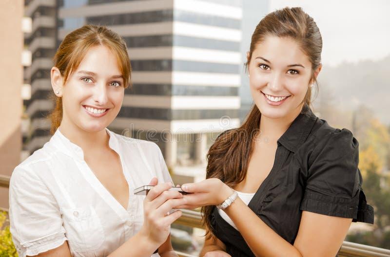 Två unga executive kvinnor som delar information royaltyfria foton