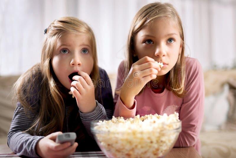 Två unga flickor äter popcorn- och klockaTV royaltyfria foton