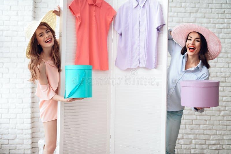 Två unga flickor på shopping Flickor väljer kläder i lagret Flickor i visningslokalen arkivbild