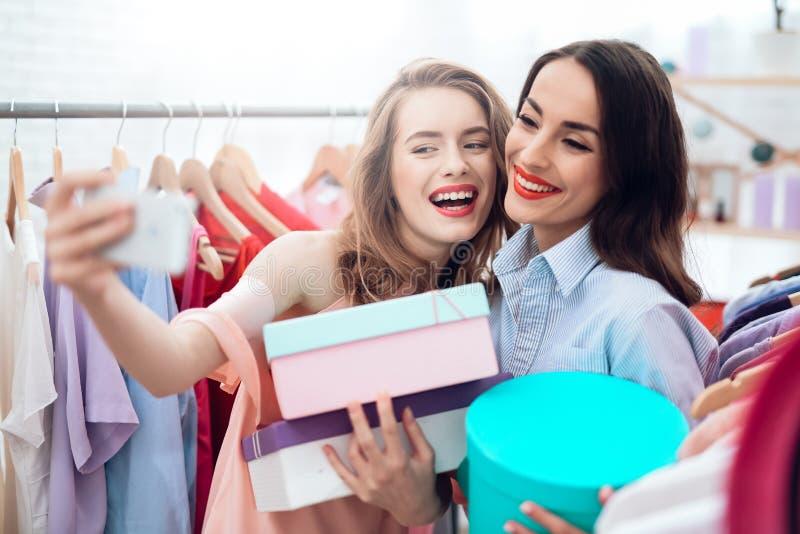 Två unga flickor på shopping Flickor väljer kläder i lagret Flickor i visningslokalen royaltyfri bild