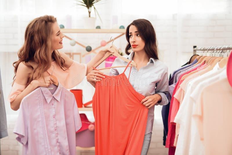 Två unga flickor på shopping Flickor väljer kläder i lagret Flickor i visningslokalen arkivfoton
