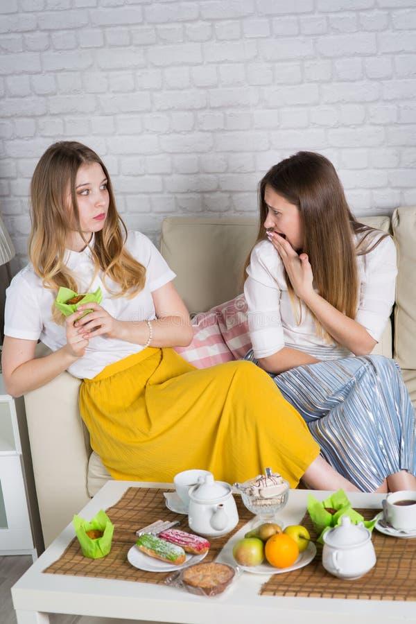 Två unga flickor sitter på soffan arkivbilder