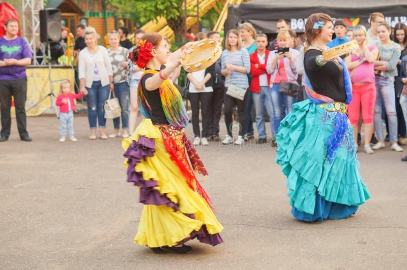 Två unga flickor som dansar zigensk dans med tamburinar arkivbild