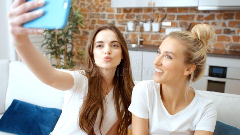 Två unga flickor som hemma gör selfie fotografering för bildbyråer