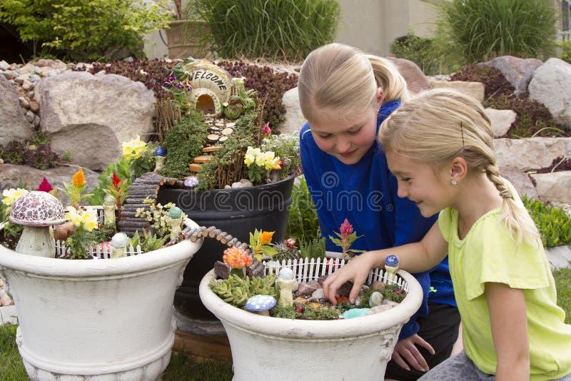Två unga flickor som hjälper att göra fen att arbeta i trädgården i en blomkruka royaltyfri foto