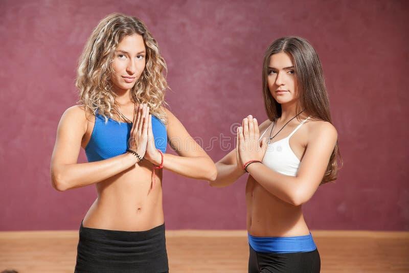 Två unga flickor som inomhus gör yoga arkivbilder
