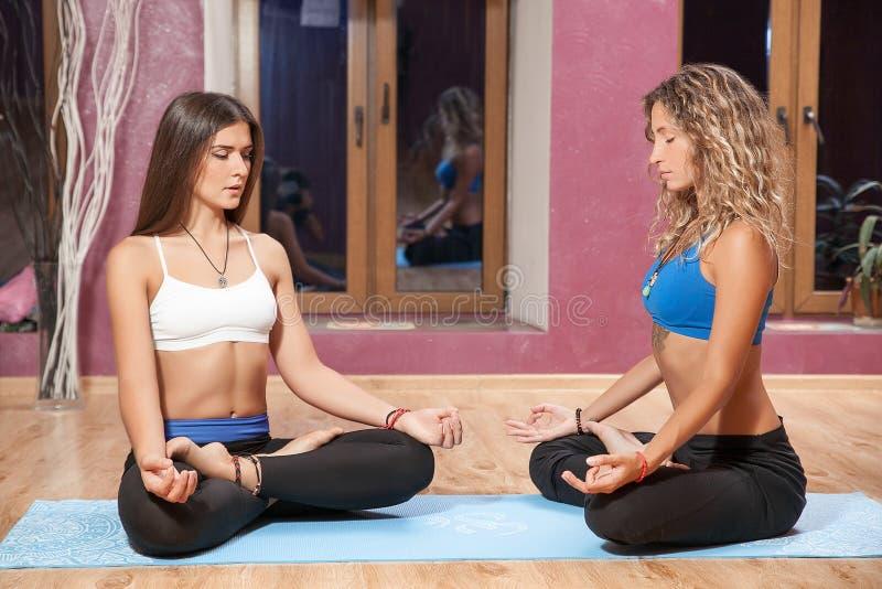 Två unga flickor som inomhus gör yoga på mattt arkivfoton