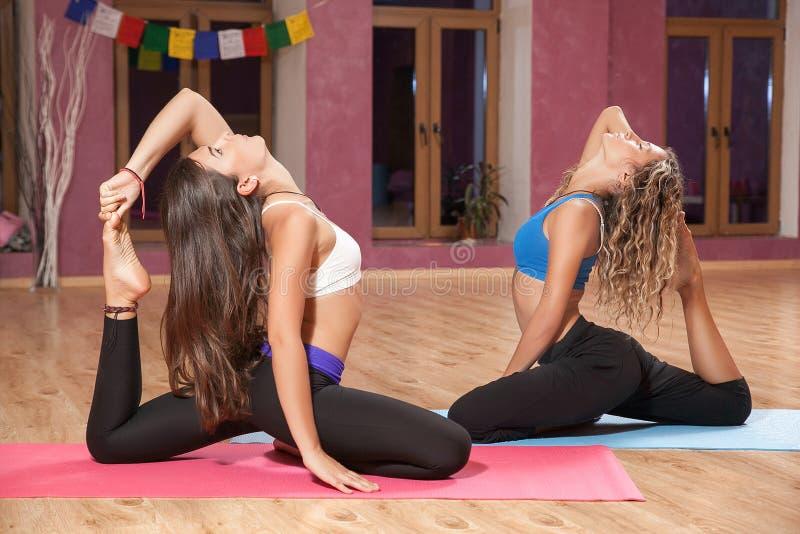 Två unga flickor som inomhus gör yoga på mattt royaltyfria foton