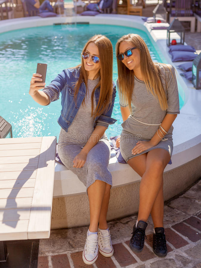 Två unga flickor som ler och tar selfie arkivbilder