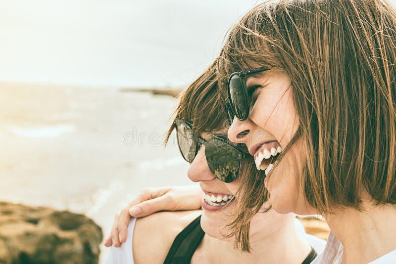 Två unga flickor som ler vid havet arkivfoto