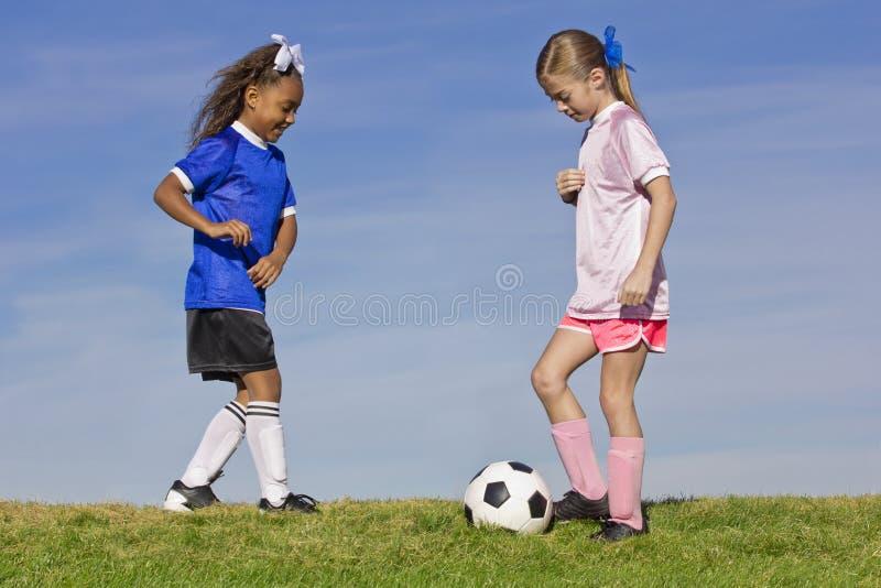 Två unga flickor som spelar fotboll fotografering för bildbyråer