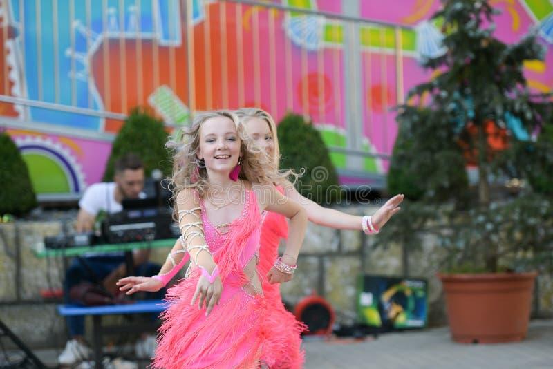 Två unga flickor som tillsammans dansar dans med nöje frilufts- danskapacitet fotografering för bildbyråer