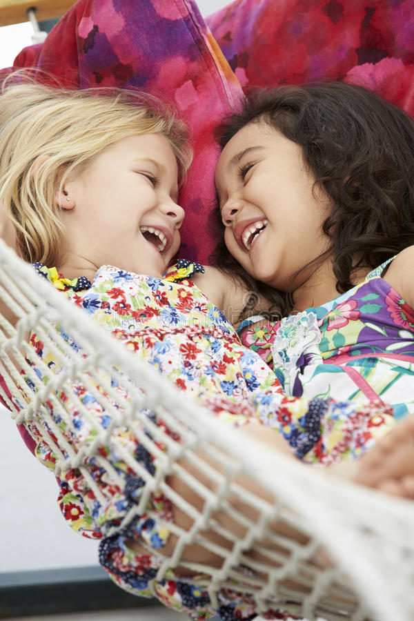 Två unga flickor som tillsammans kopplar av i trädgårds- hängmatta fotografering för bildbyråer