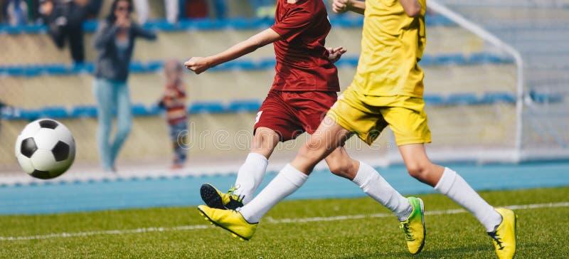 Två unga fotbollspelare som sparkar bollen på fotbollfält Fotbollhorisontalbakgrund royaltyfri bild