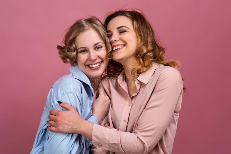 Två unga gladlynta flickavänner skratt och kram Kamratskap, systrar, förhållanden och realitetsinnesrörelser från kommunikation royaltyfri fotografi