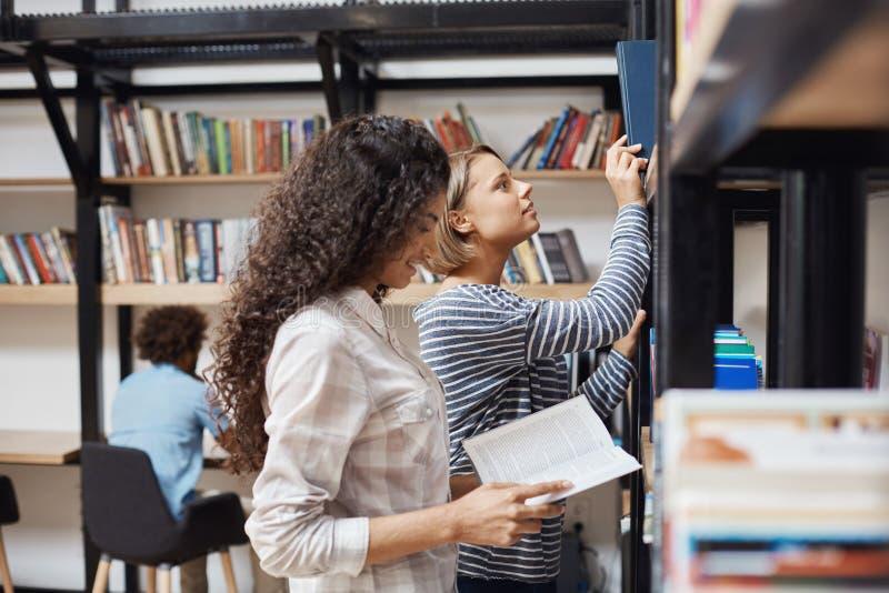Två unga gladlynta kvinnliga studenter i tillfällig kläder som står near bokhyllor i universitetarkivet som igenom ser royaltyfria foton