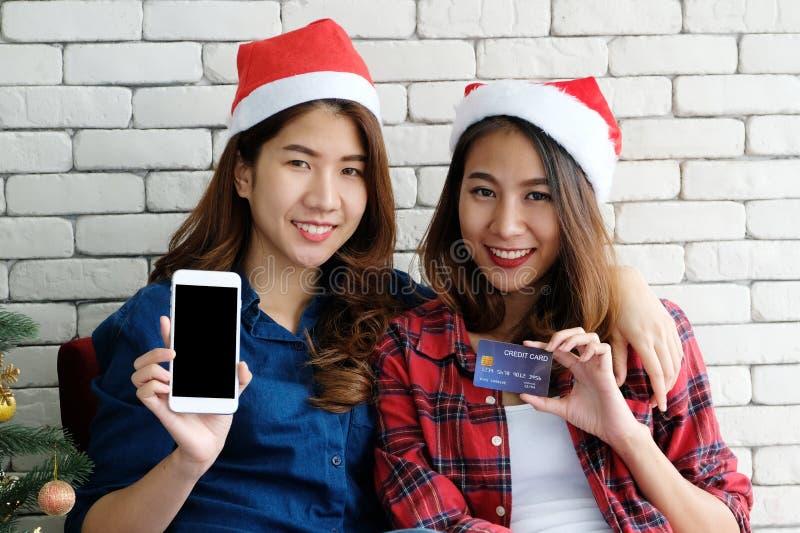 Två unga gulliga asia kvinnor som rymmer smartphonen med tom skärm a arkivfoto