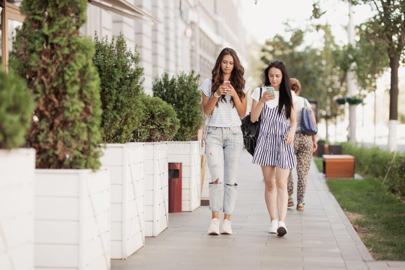 Två unga gulliga slanka flickor med långt hår, går ner gatan på en solig dag arkivfoto