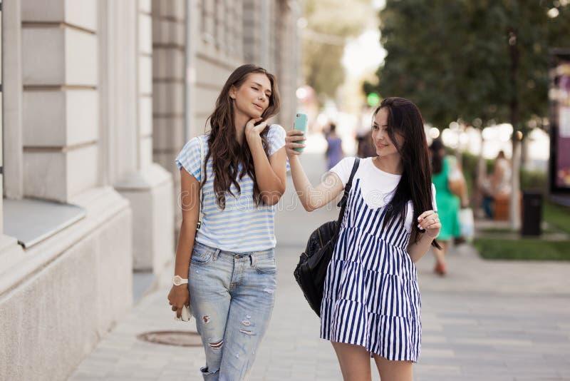 Två unga gulliga slanka flickor med långt hår, går ner gatan på en solig dag royaltyfri foto