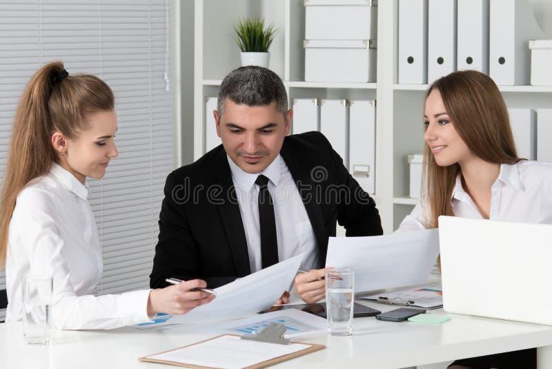 Två unga härliga affärskvinnor som konsulterar med deras colleag arkivfoton