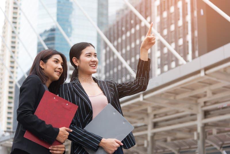 Två unga härliga affärskvinnor som pekar och ler med utomhus- bakgrund Aff?rs- och sk?nhetbegrepp M?te och h?lsning royaltyfri bild