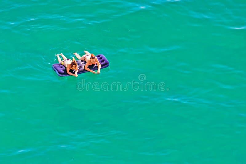 Två unga härliga Caucasian kvinnor i bikini som solbadar och kopplar av att ligga på madrassen i lugna azurt vatten av Black Sea royaltyfria foton