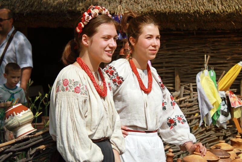 Två unga härliga flickor i den utomhus- etniska byn Pirogovo, Ki royaltyfria foton