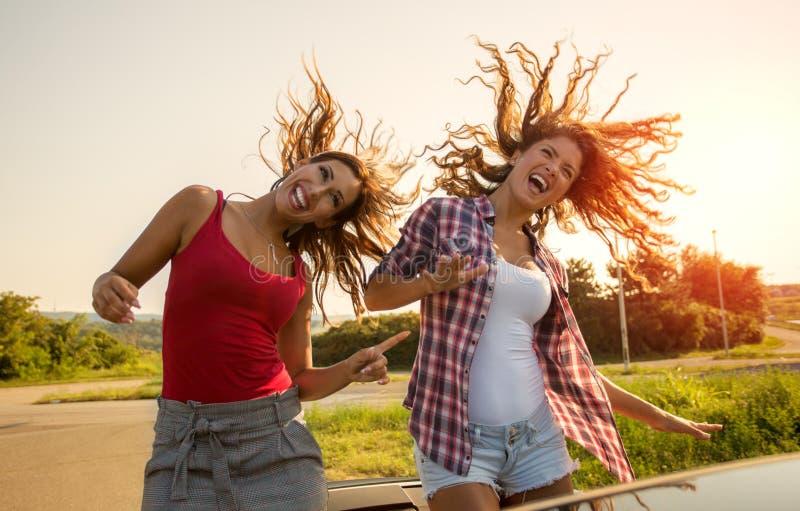 Två unga härliga flickor som har gyckel i en konvertibel bilshakin arkivbilder