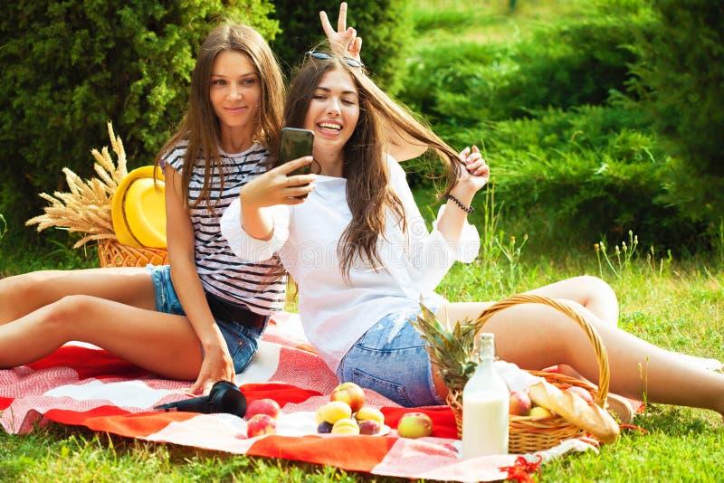 Två unga härliga flickor som har gyckel på picknicken som gör upp selfie på ett smartphoneslut arkivbilder