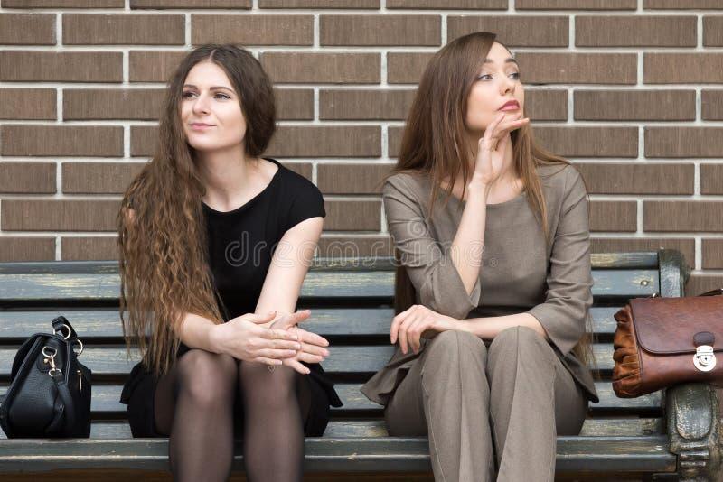 Två unga härliga kvinnligrivaler på bänk fotografering för bildbyråer