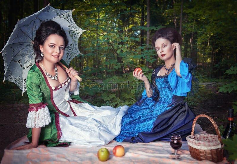 Två unga härliga kvinnor i medeltida klänningar som har picknicken arkivfoto