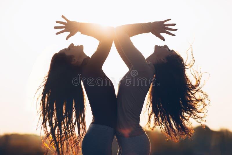 Två unga härliga kvinnor som gör yogaasana i solljus royaltyfri fotografi
