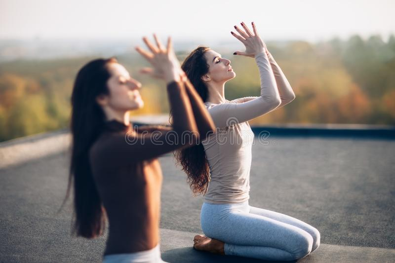 Två unga härliga kvinnor som gör yogaasana på det utomhus- taket arkivbilder