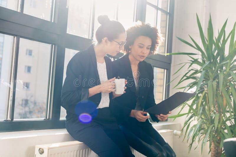 Två unga kollegor som granskar affärsrapporter under avbrott royaltyfria foton
